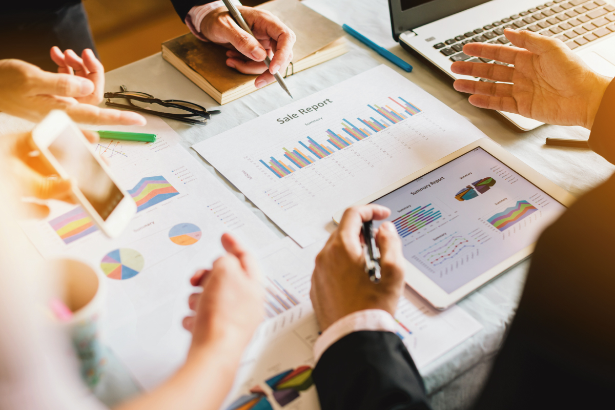 Three businessman investment consultant analyzing company financial report balance sheet statement working with documents graphs
