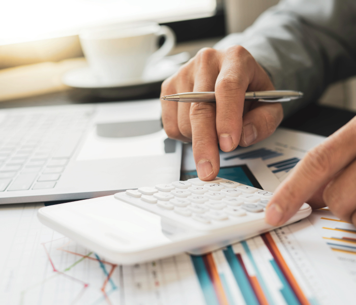 Man's hand using calculator on desk with laptop and financial graphs