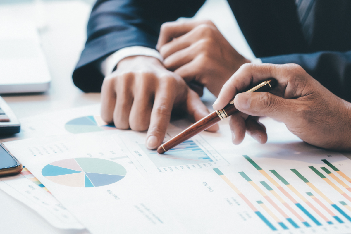 Two business people meeting together Pointing to the graph assess business profits